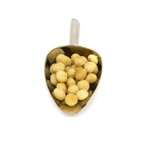 Nerezová lopatka s jádry makadamových ořechů.
